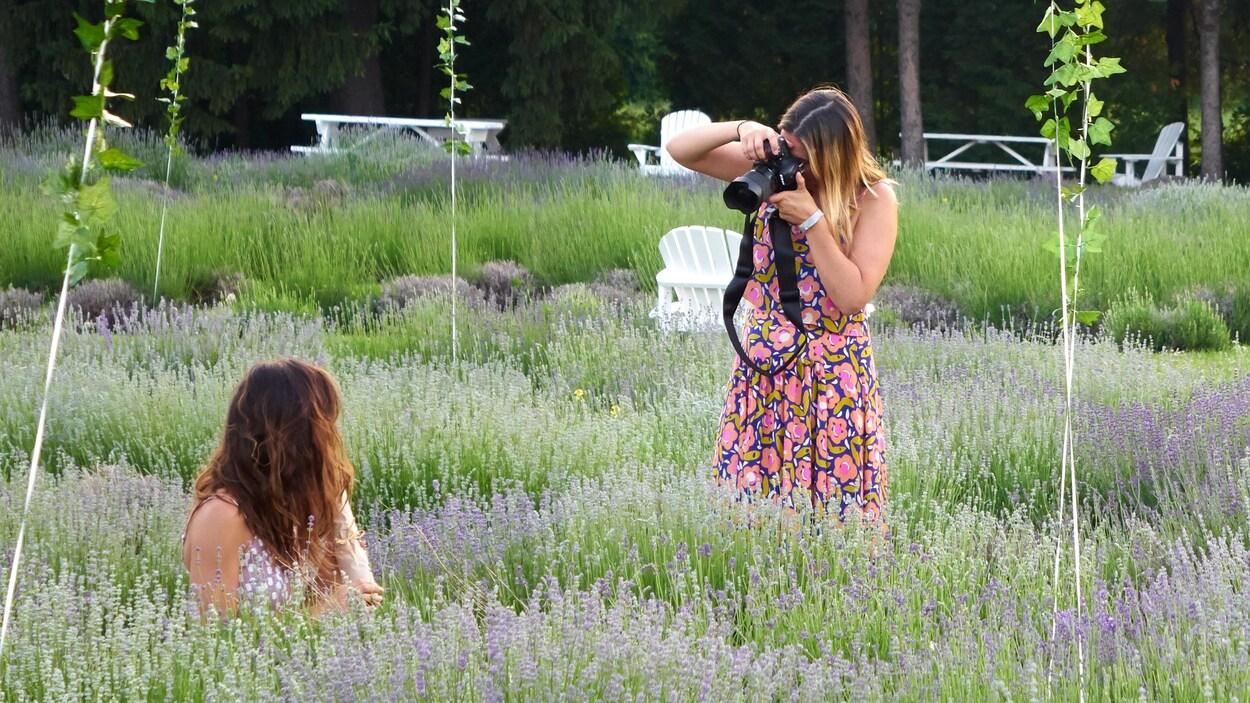 Une jeune femme se fait photographier en contre-plongée de dos dans un champ de lavande. Des ballons enjolivent la scène.