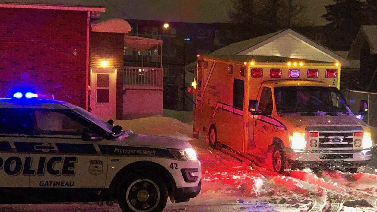 Une ambulance et un véhicule du Service de police de la Ville de Gatineau stationnés près d'un immeuble en hiver, la nuit.