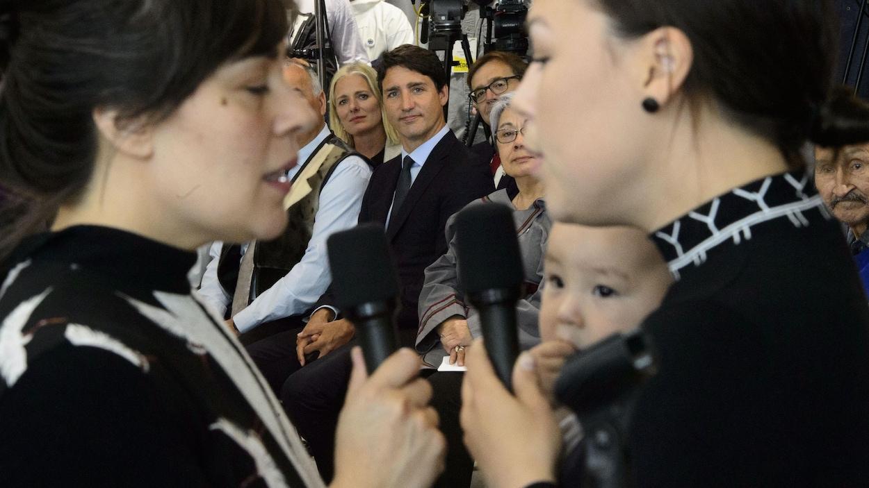Deux femmes chantent devant Justin Trudeau assis sur une chaise.