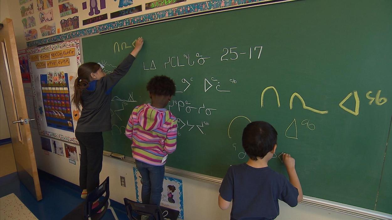 Des élèves écrivent au tableau en inuktitut.