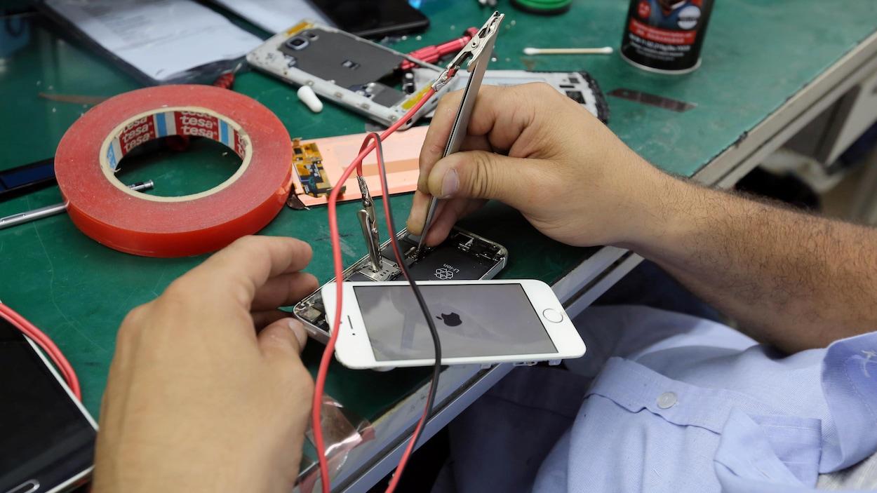 Un technicien répare un iPhone 7.