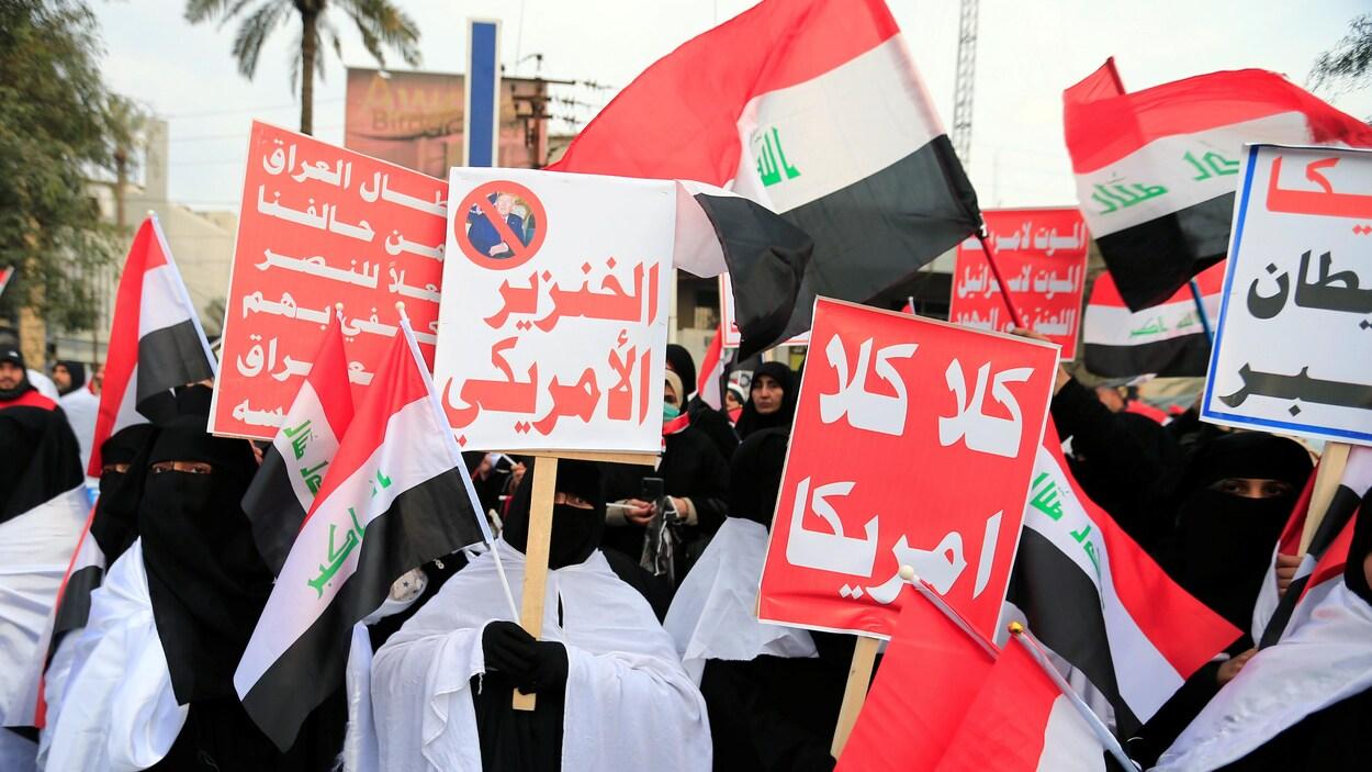 Des manifestants avec des pancartes blanches, d'autres rouges et des drapeaux irakiens.