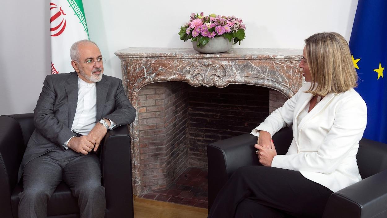 Assis dans des fauteuils, Mohammad Javad Zarif et Federica Mogherini se parlent.
