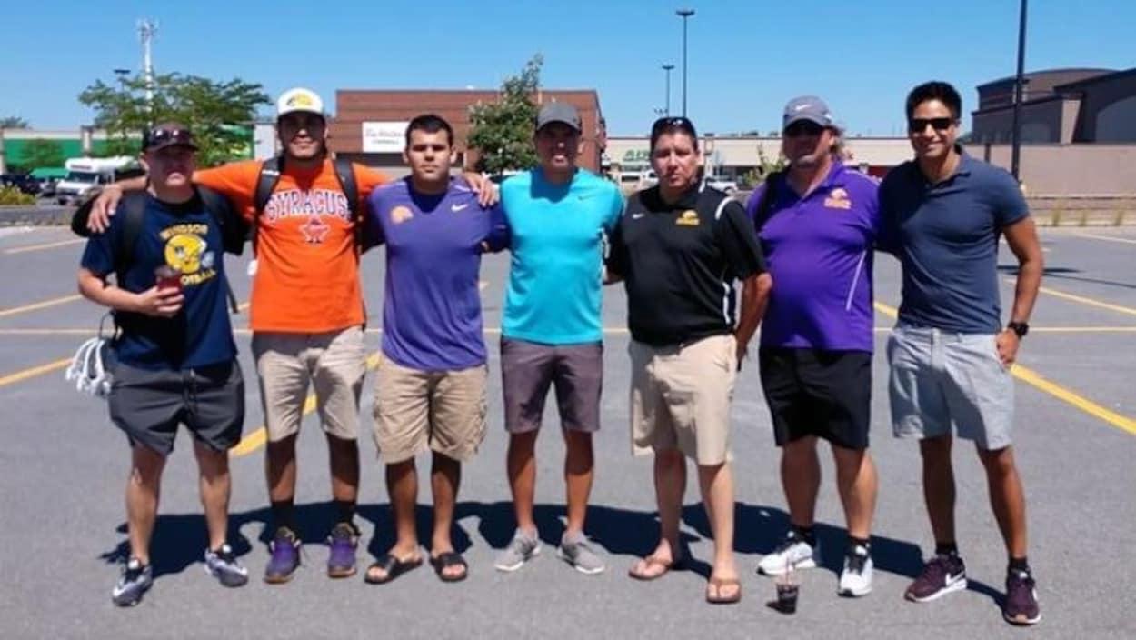 Des joueurs mohakws des Iroquois Nationals et leurs entraîneurs posent dans un stationnement avant leur départ.