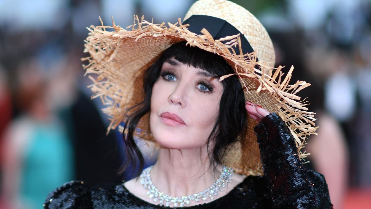 La femme porte un chapeau de paille et lève la main.