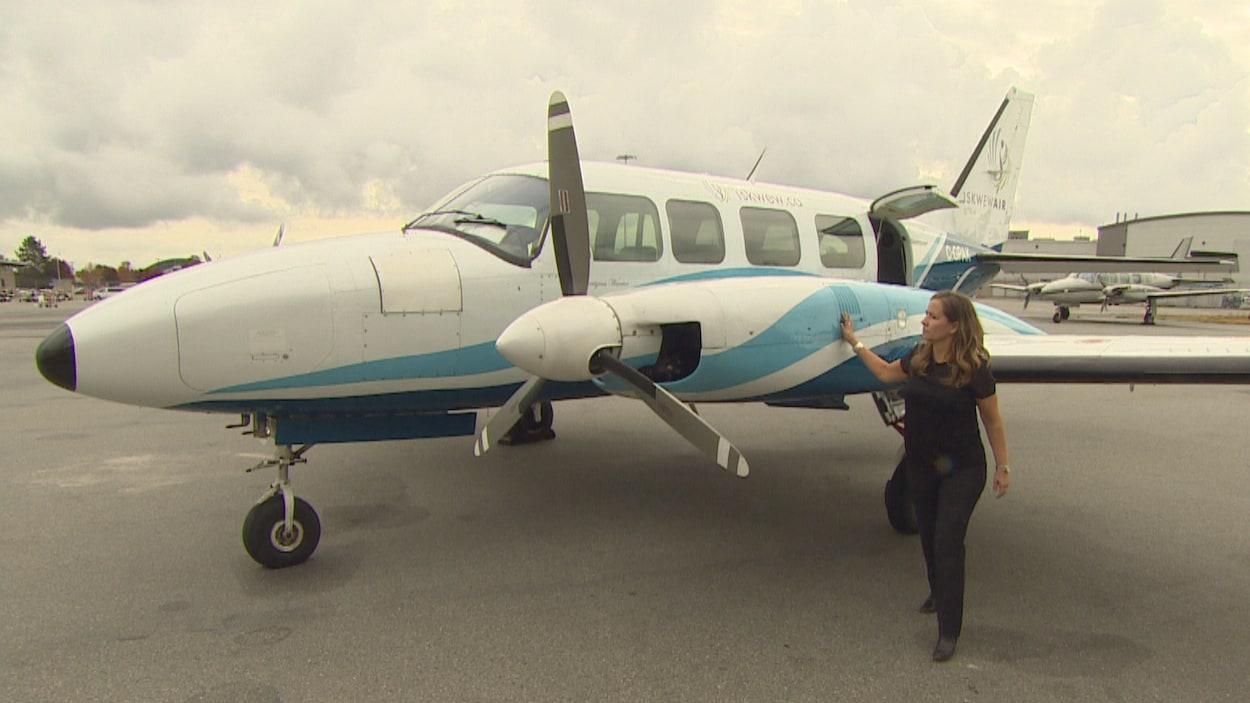 Teara Fraser debout à côté du premier avion de sa compagnie.