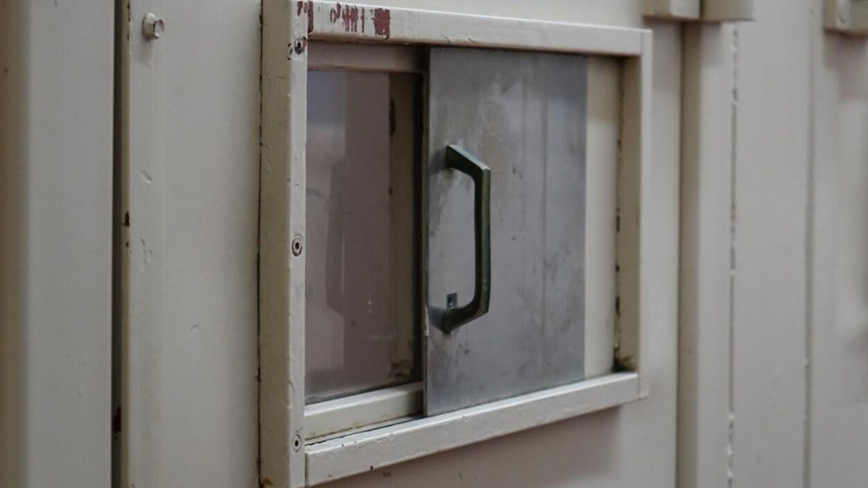 Photo d'une petite fenêtre dans une porte de prison.