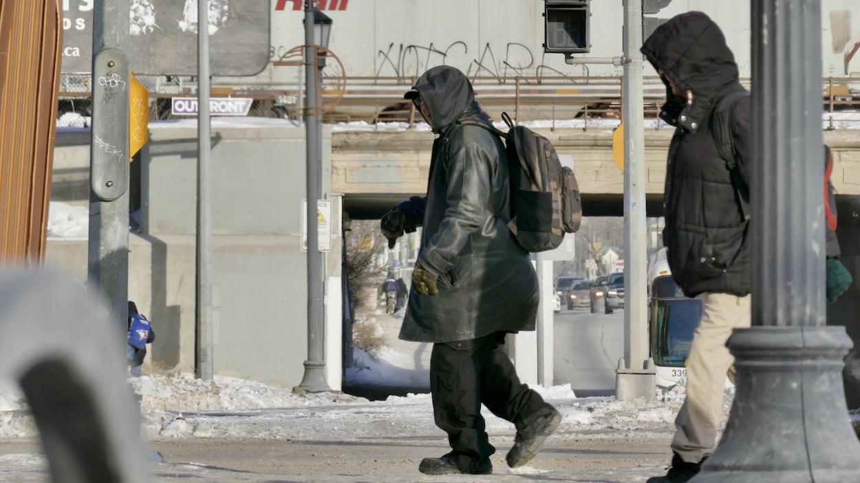Un homme traverse une rue.