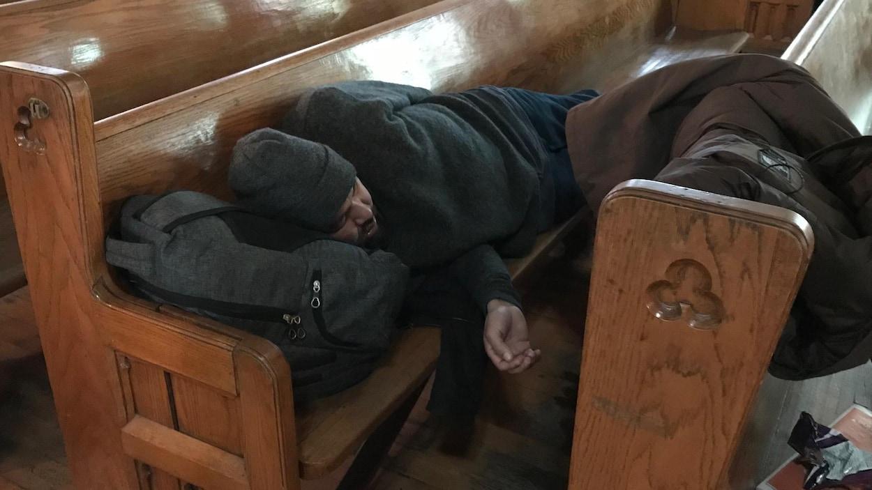 Une personne est allongée sur un banc, la tête appuyée sur son sac.