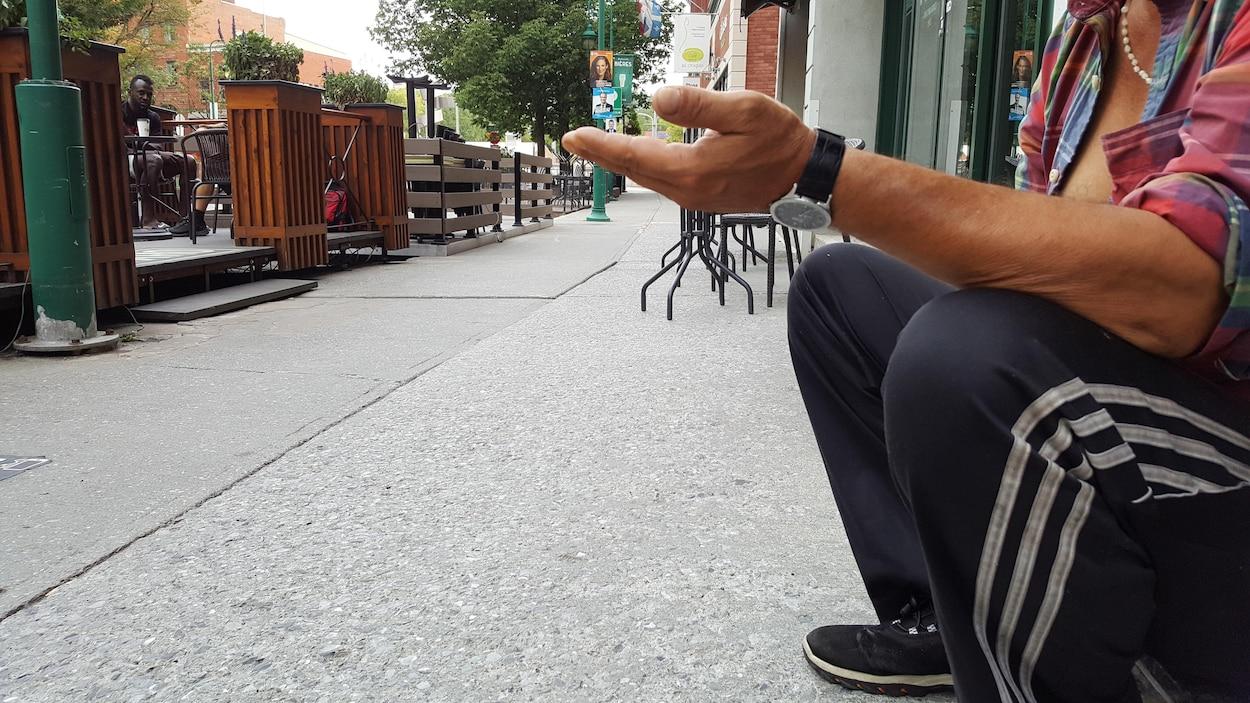 Une personne itinérante qui mendie au centre-ville de Sherbrooke