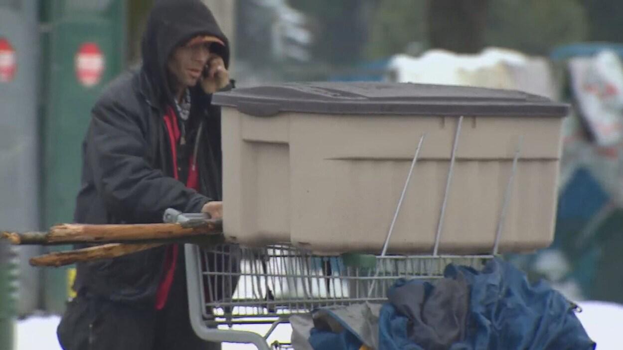 Une personne pousse un chariot avec une boîte en plastique et une tente, et parle au téléphone.