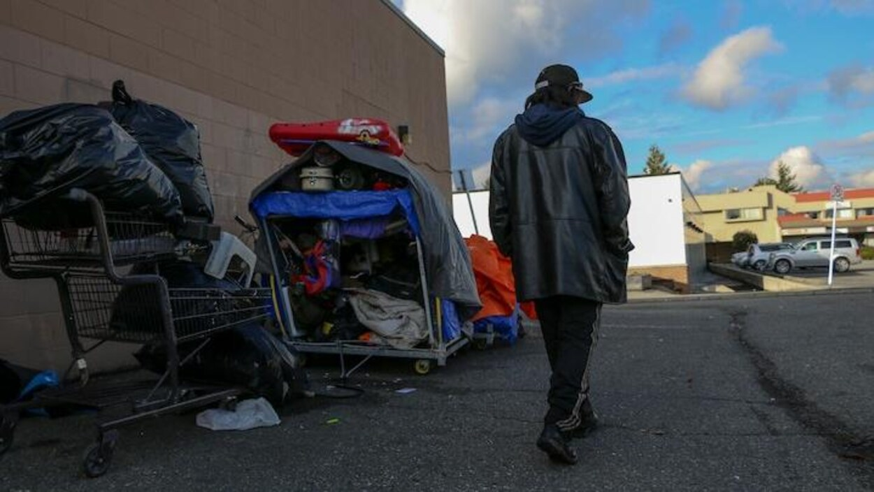 Un homme de dos sur la rue près d'un immeuble avec un panier d'épicerie rempli de matériel hétéroclite à ses côtés.