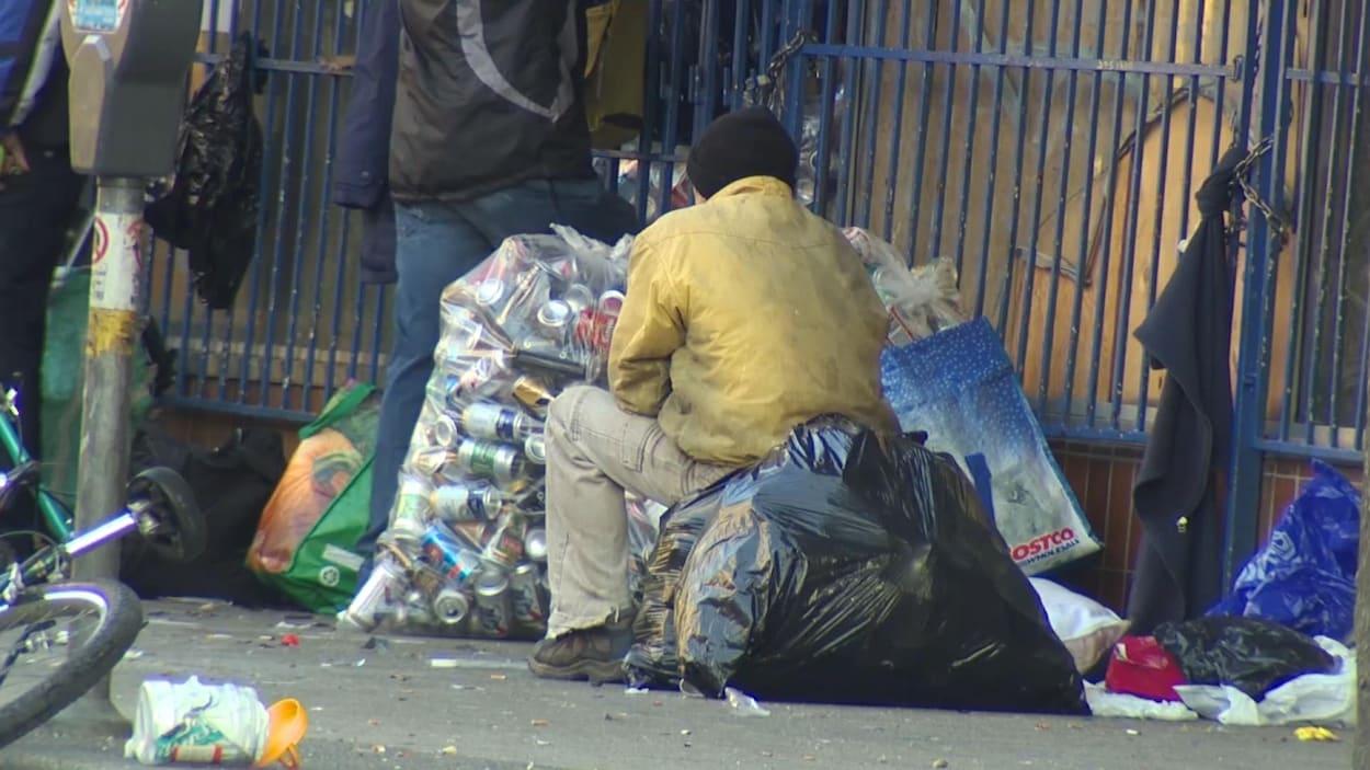 Un homme assis sur un sac poubelle contenant des canettes, d'autres sacs l'entourent sur le trottoir.