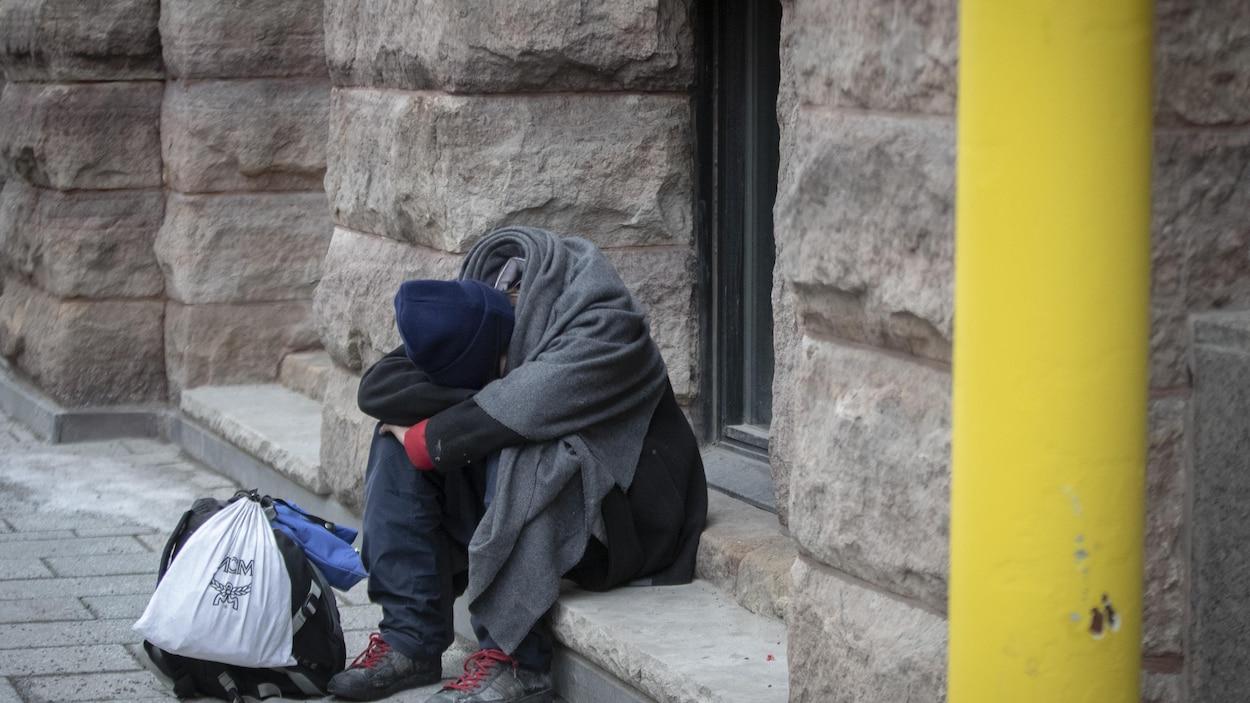 Une homme assis sur une marche, la tête entre les bras.