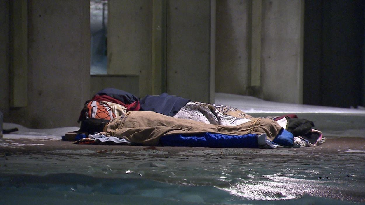 Un sans-abri dormant sur le sol, en plein hiver.