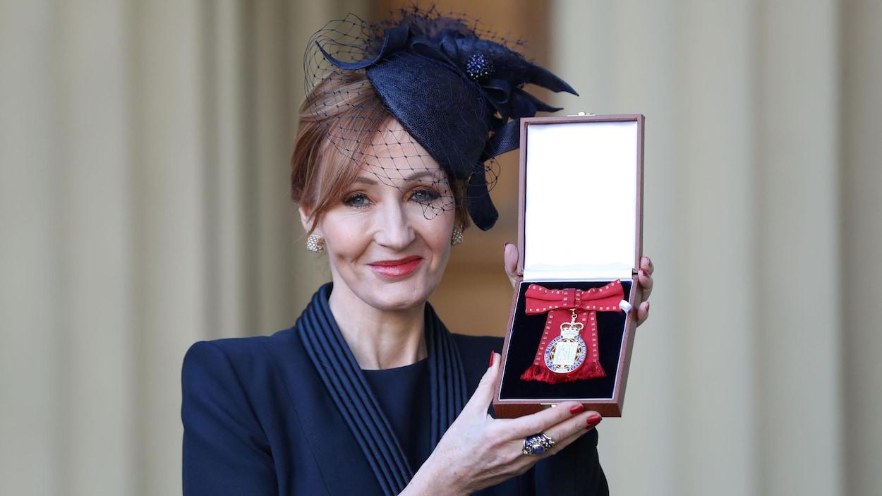 J.K. Rowling en habits élégants arbore une médaille au palais de Buckingham.