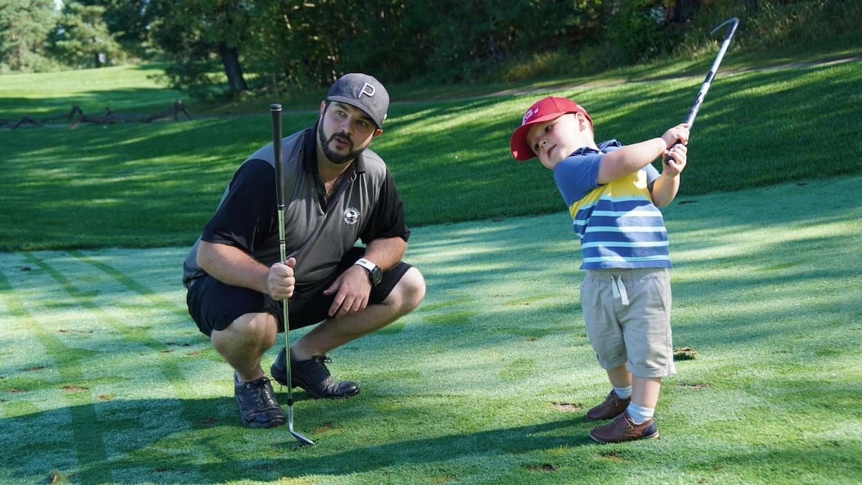 Un homme et son fils sur un terrain de golf.