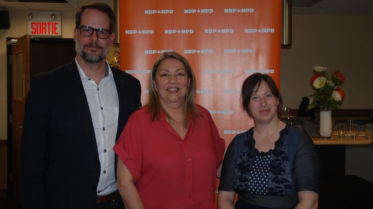 Alexandre Boulerice et Christine Moore posent avec une femme devant une affiche du NPD.