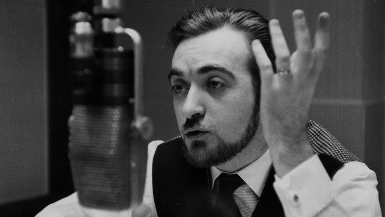 L'animateur parle et gesticule, derrière le micro, dans un studio de radio.