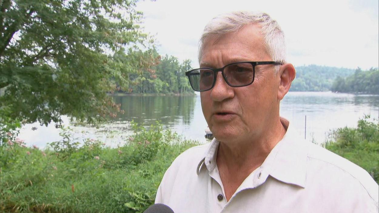 Jacques Laurin en entrevue devant une rivière et des arbres.