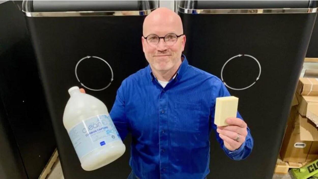 Jaeson Cardiff tient à la main du savon liquide et un pain de savon produits avec du CO2 tiré d'une technologie qu'il a développé.