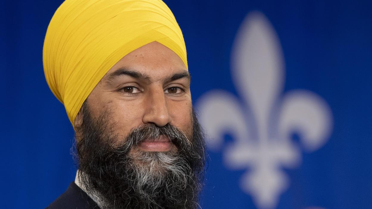 Jagmeet Singh sourit devant un drapeau du Québec.