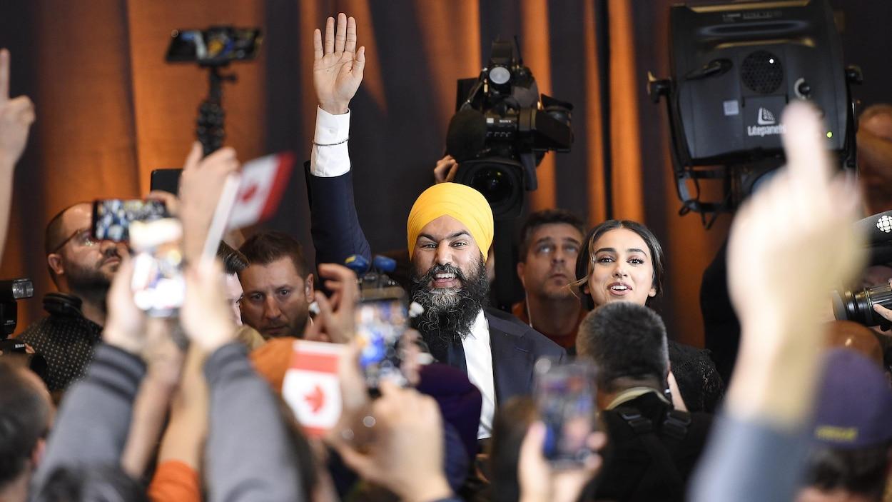 Jagmeet Singh salue la foule à son arrivée avec sa femme.