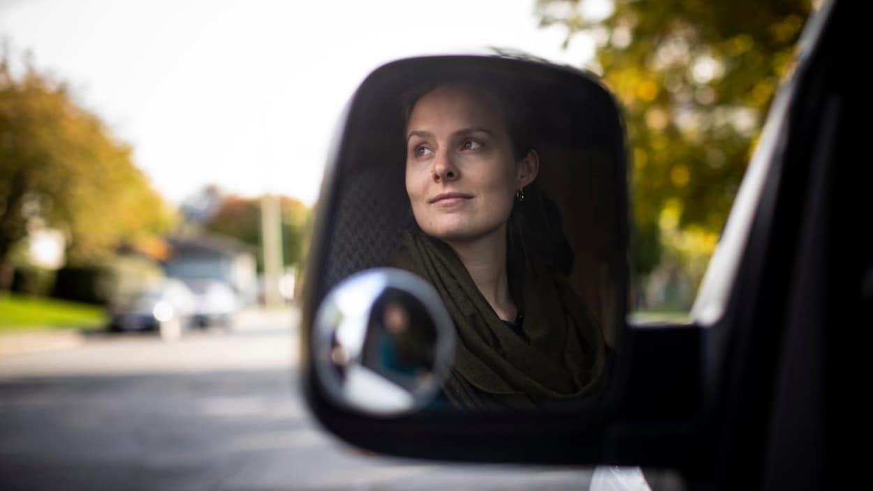 Un rétroviseur reflète l'image de Jaklyn De Vos.
