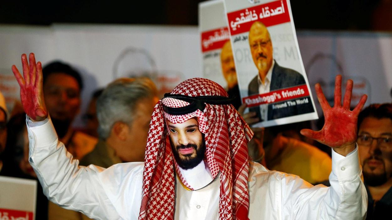 Un homme portant un masque de Mohammed ben Salmane lève ses deux mains peintes en rouge. Derrière lui, des gens brandissent des photos de Jamal Khashoggi.