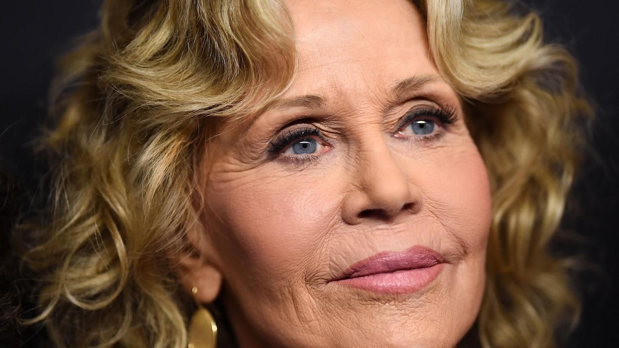 Une femme d'âge mûr aux cheveux blonds bouclés et aux yeux bleus.