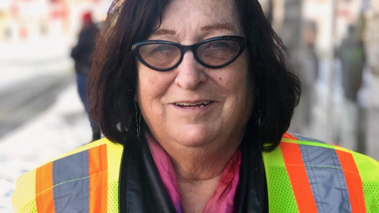 Jane Scharf qui porte un gilet jaune fluorescent dans une rue du centre-ville d'Ottawa