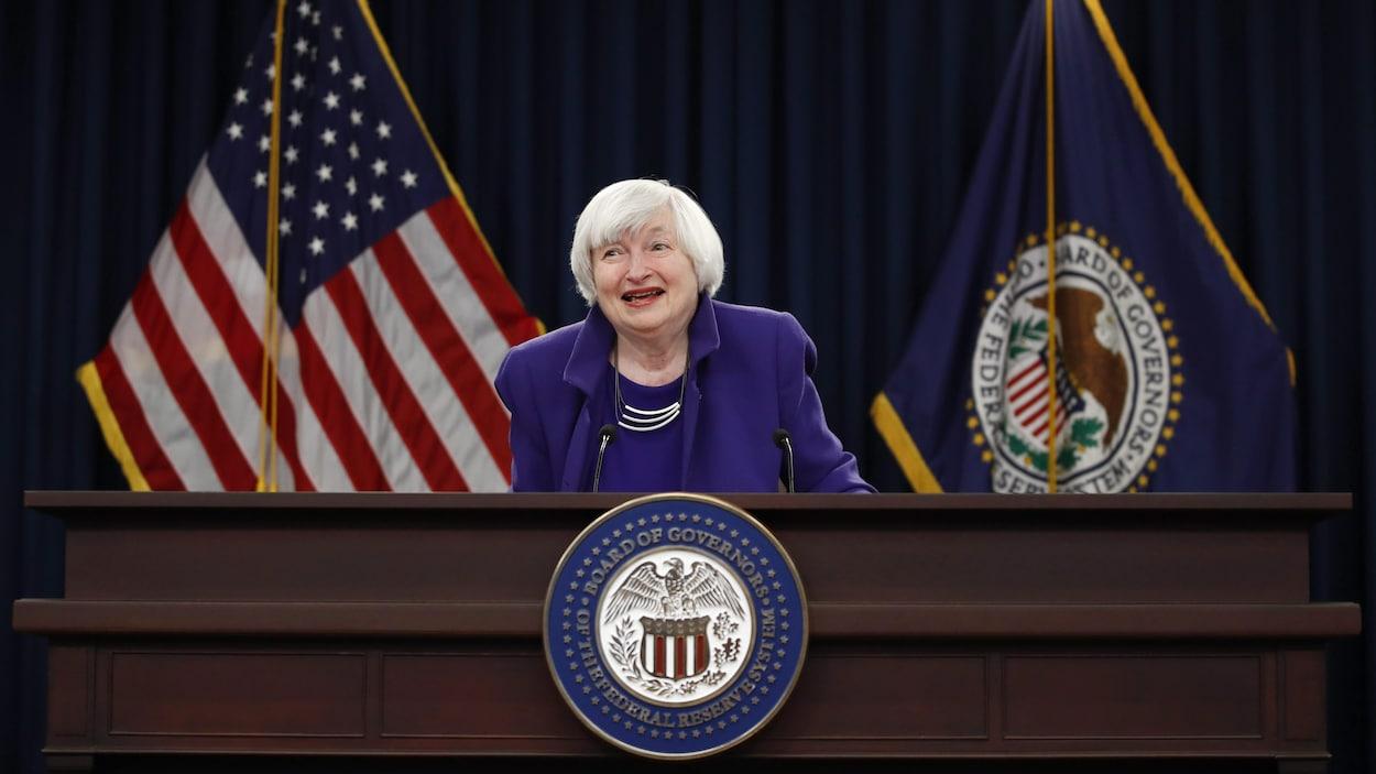 Janet Yellen est derrière un lutrin portant le sceau de la Fed et devant des drapeaux des États-Unis et de la Fed.