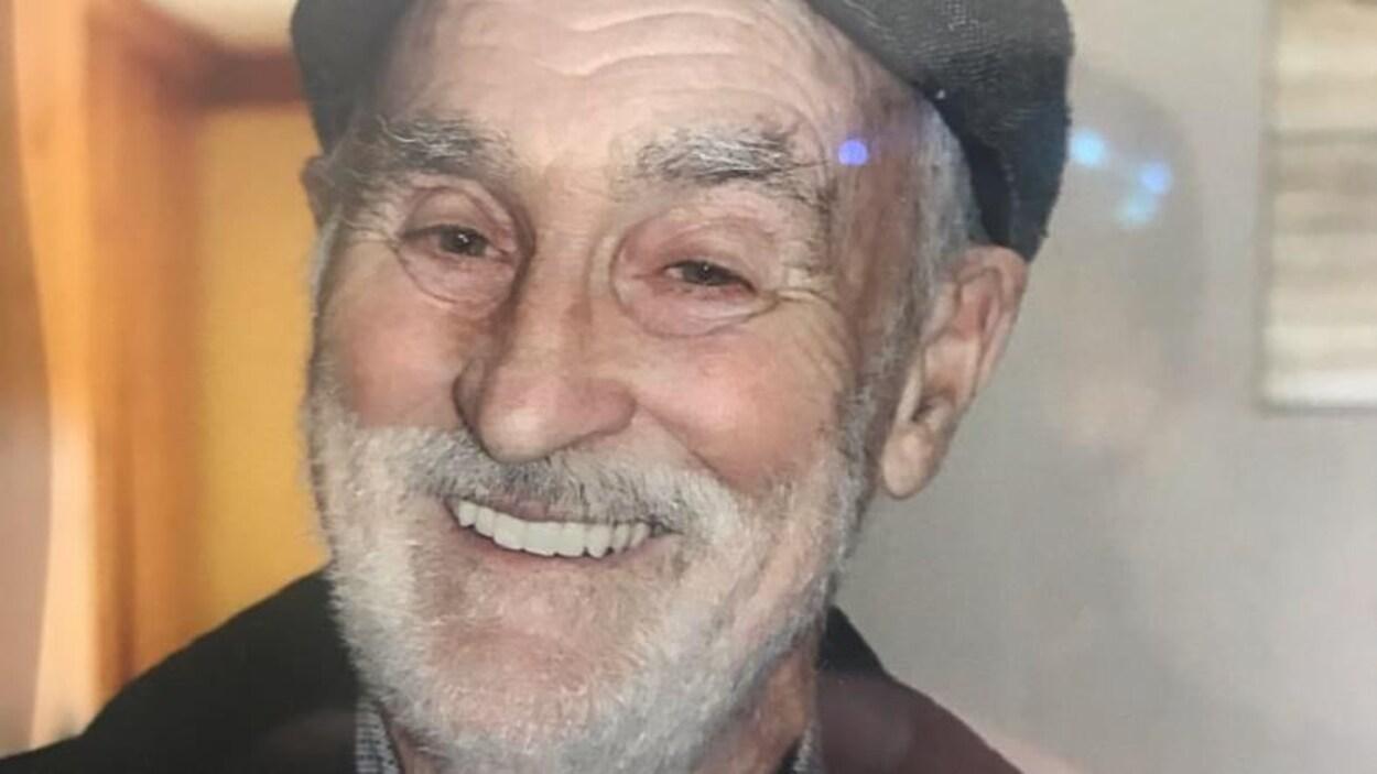 Janvier Leroux qui sourit. L'homme porte une casquette et a une barbe blanche.