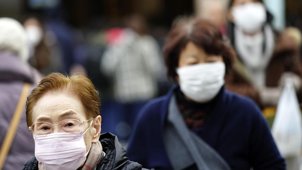Deux passantes à Tokyo portant des masques blancs sur leur visage.