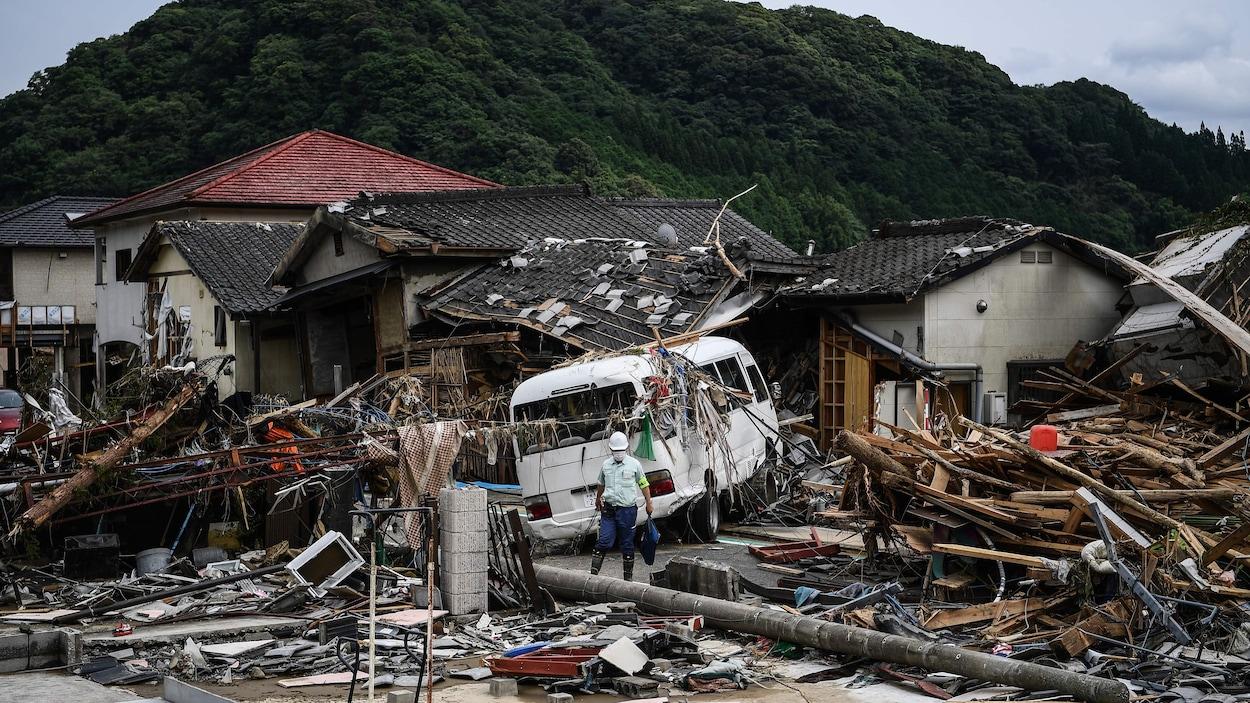 Un homme marche devant des maisons endommagées après des pluies torrentielles et des inondations au Japon.