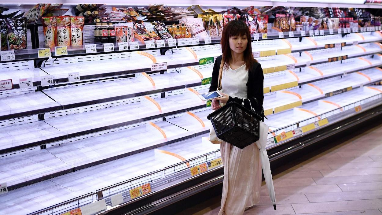 Une consommatrice passe le long de présentoirs vides dans un magasin de Tokyo.