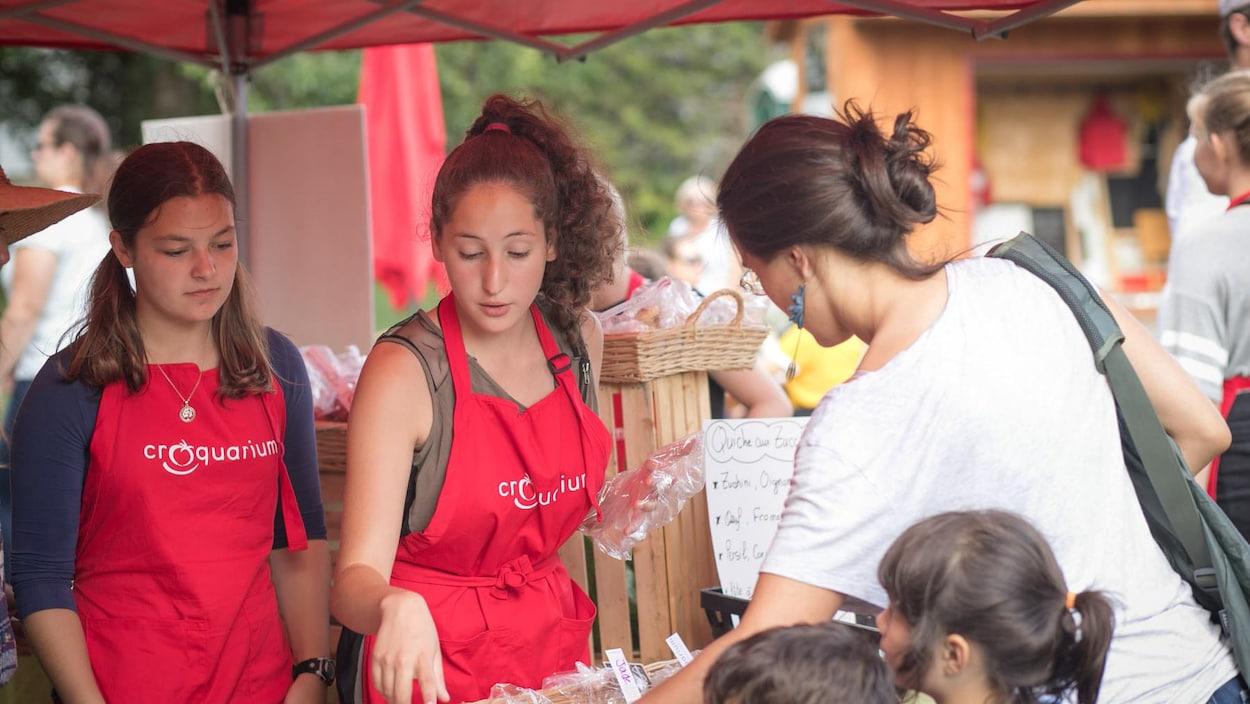 Deux jeunes qui vendent leurs produits dans un marché public.