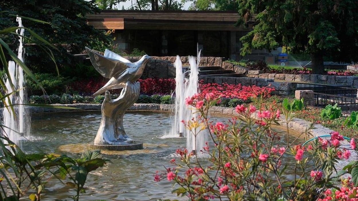 Une sculpture dans une fontaine entourée de fleurs.