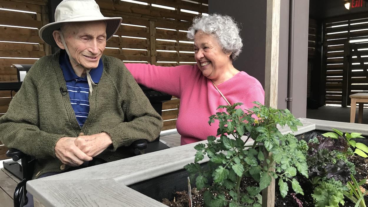 Un couple de personnes âgées devant un potager.