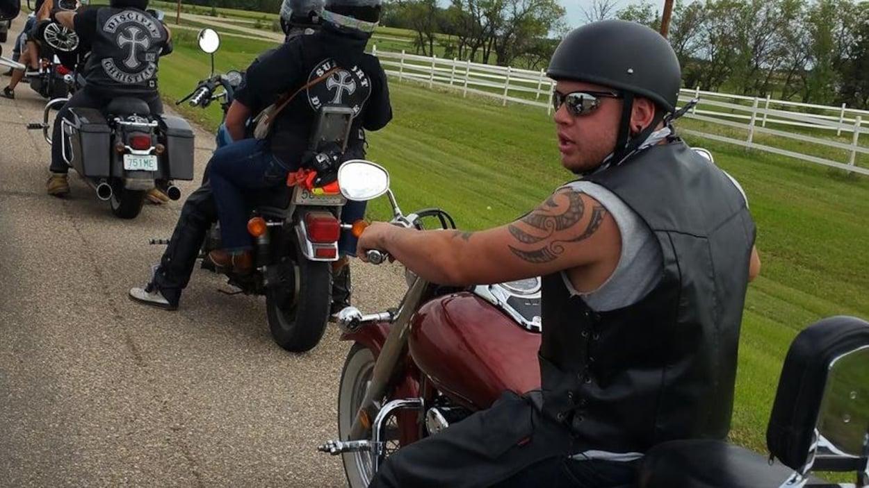 Jared Robertson sur une moto porte une combinaison de motard et se trouve sur une fille avec plusieurs autres motards devant lui.