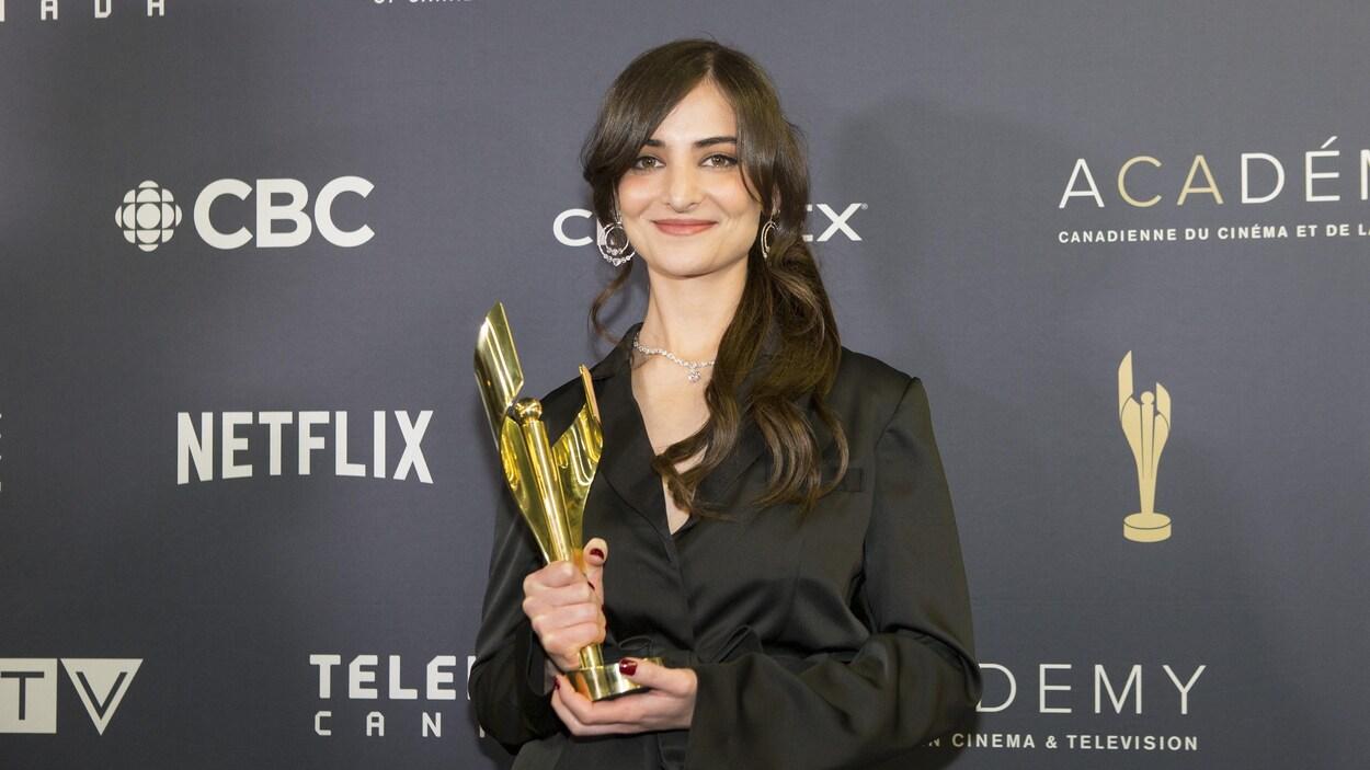 La femme pose en souriant avec son trophée.