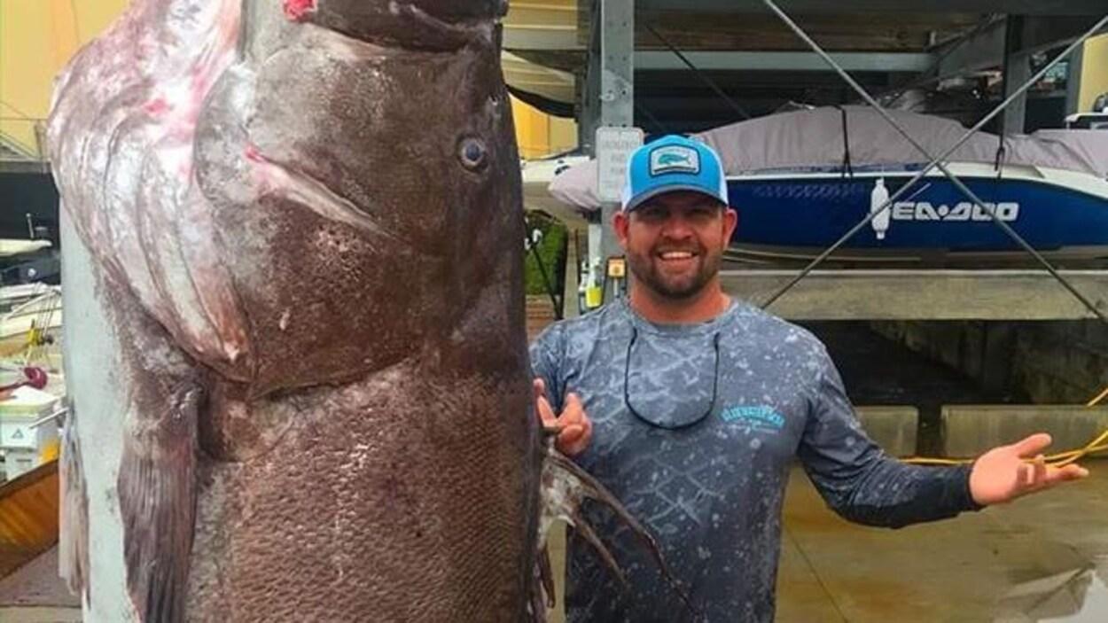 Un homme souriant se tient à côté d'un énorme poisson suspendu à un crochet.