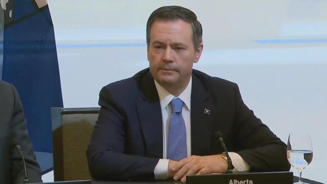 Jason Kenney est assis à une table pour répondre aux questions des journalistes.