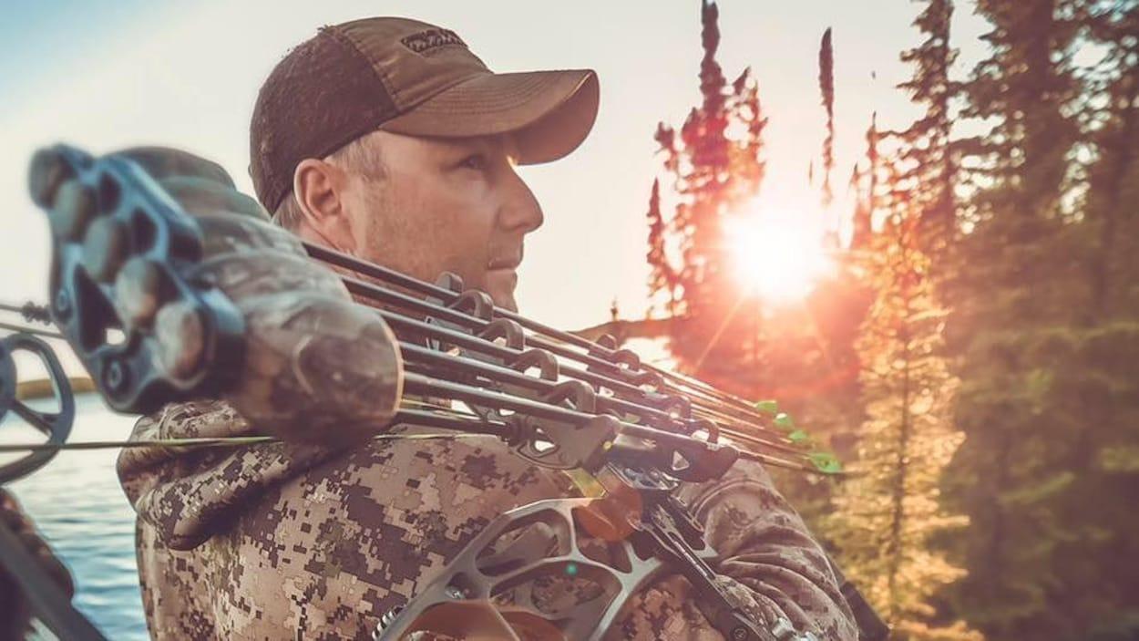 Le chasseur Jason Peterson en tenue de chasse et portant une casquette au bord d'un plan d'eau