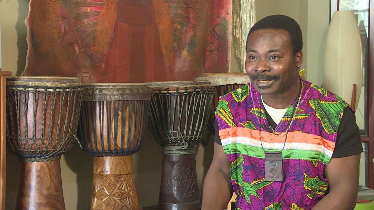 Jean avec porte un vêtement traditionnel de Côte d'Ivoire. Derrière lui, se trouvent 4 grands tambours.