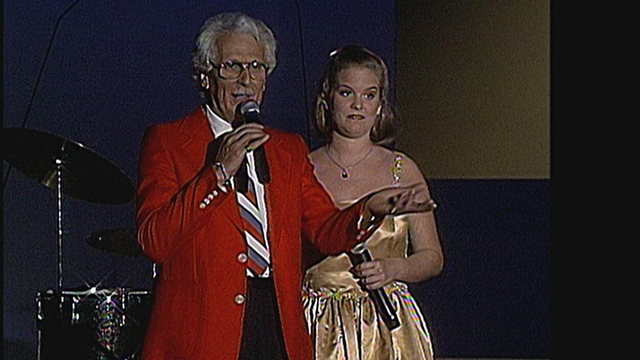 Jean-Bernard Rainville est sur une scène vêtu d'un veston rouge, accompagné d'une femme.