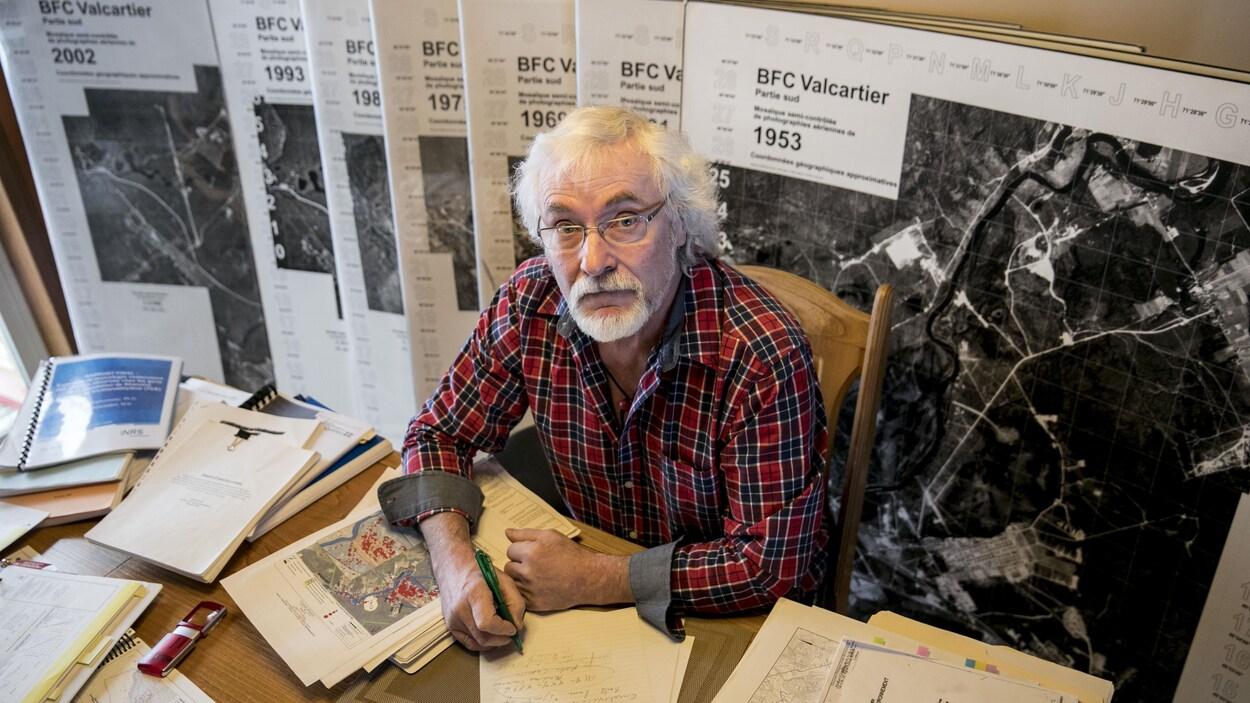 Jean Bernier assit à son bureau avec des documents liés à la contamination au TCE de l'eau potable de certains résidents