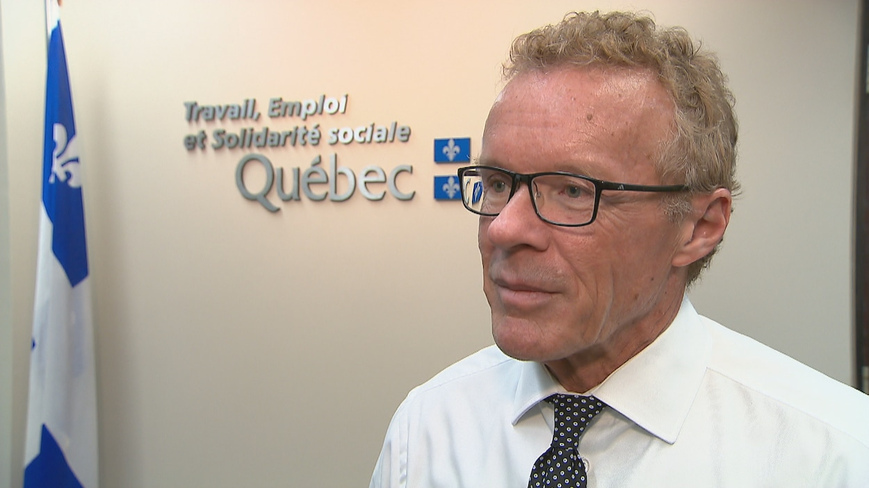 Le ministre Jean Boulet pose devant un drapeau du Québec.