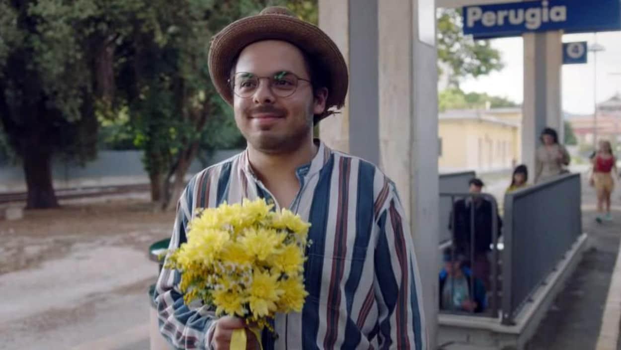 Jean-Carl Boucher tient un bouquet de fleurs jaunes dans une scène du film <i>1991</i>.