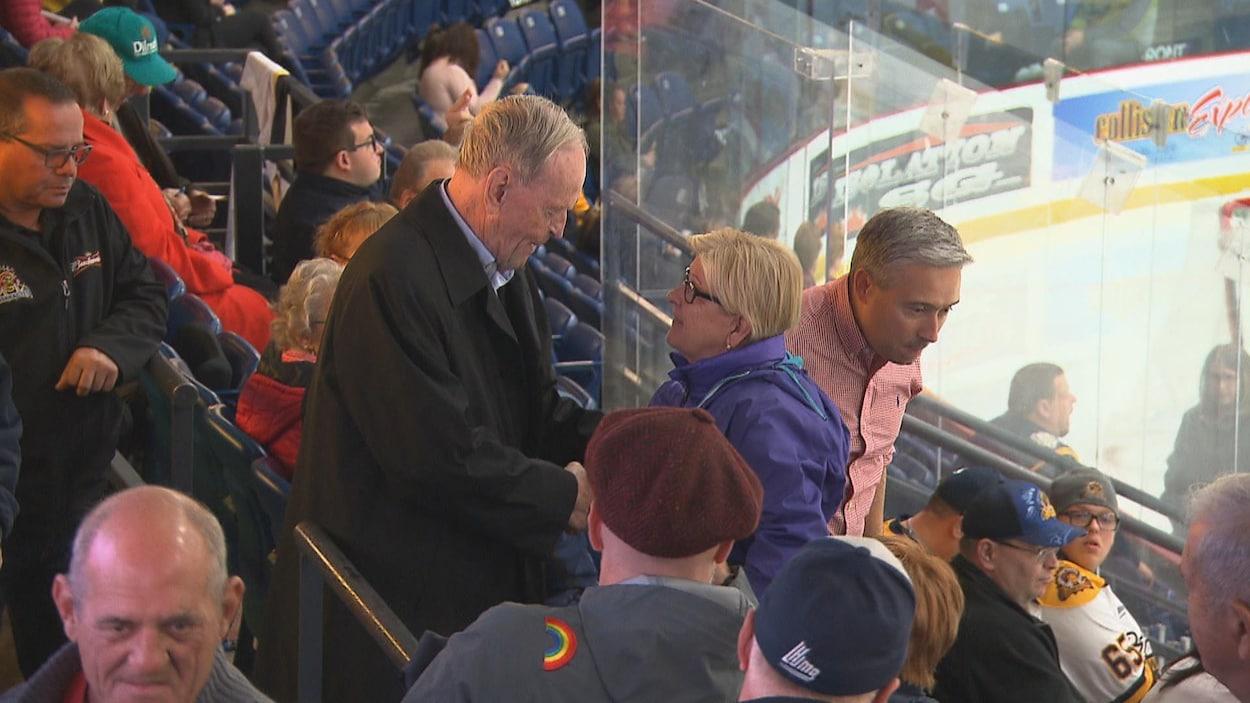Un homme serre la main d'une femme dans les gradins d'un aréna.